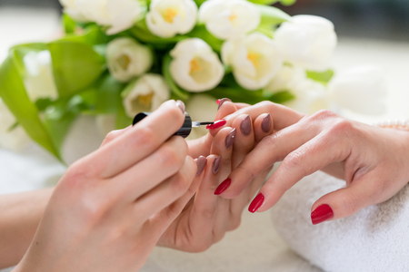 Foto de Close-up of the hands of a skilled manicurist applying elegant red nail polish, on the medium length nails of a young woman in a trendy beauty salon - Imagen libre de derechos