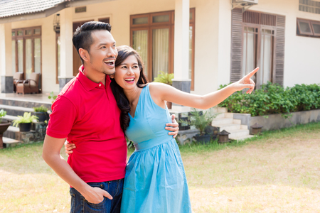 Foto de Cheerful young couple looking in the same direction in front of a cozy residential property - Imagen libre de derechos