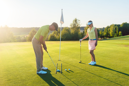 Foto de Full length side view of a man ready to hit the golf ball into the hole while exercising the short shot, with his game partner in a modern country club in summer - Imagen libre de derechos
