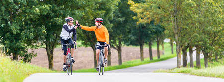 Photo for Racing cyclists after sport and fitness workout giving high five in finish - Royalty Free Image