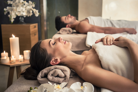 Photo for Young man and woman lying down on massage beds at Asian luxury spa and wellness center - Royalty Free Image