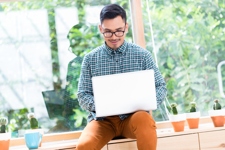 Foto de Relaxed young Asian employee working on laptop while sitting on a wooden drawer in the office - Imagen libre de derechos