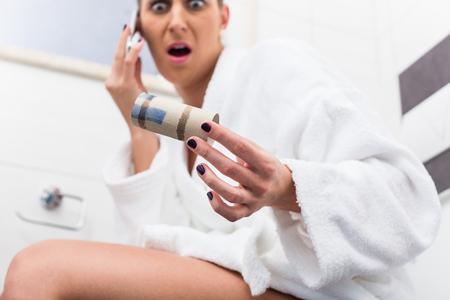 Foto de Woman in bathroom sitting on toilet and complaining via phone about lack of paper - Imagen libre de derechos