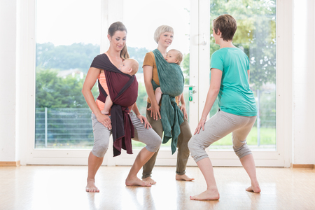 Foto de Young women wearing babies for mother-child bonding and doing pelvis floor exercises - Imagen libre de derechos