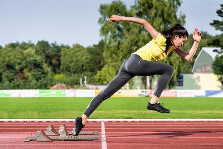 Photo pour Female sprinter leaving starting blocks on running track in stadium - image libre de droit