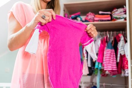 Foto für Soon-to-be mom shows girls clothes with anticipation in baby room - Lizenzfreies Bild