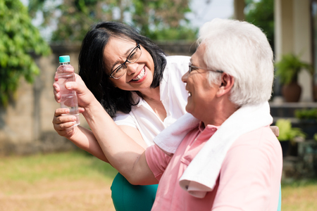 Photo pour Careful senior woman giving a bottle of water to her partner outdoors in a summer day - image libre de droit