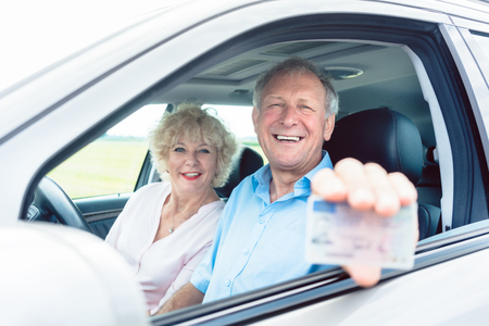 Foto de Portrait of a happy senior man showing his available driving license while sitting in the car next to his cheerful wife - Imagen libre de derechos