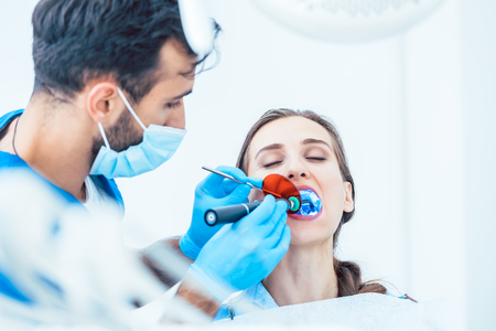 Photo pour Young woman during innovative oral treatment with cordless LED curing light machine for whitening and restoration in the dental office of an experienced dentist - image libre de droit