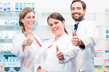 Photo for Pharmacists in pharmacy showing thumbs up and smiling - Royalty Free Image