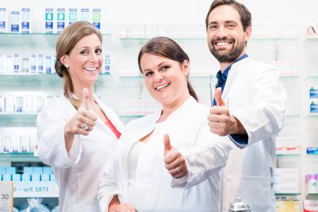 Foto de Pharmacists in pharmacy showing thumbs up and smiling - Imagen libre de derechos