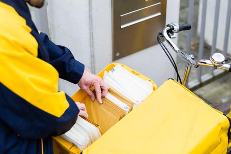 Foto de Postman delivering letters to recipient mailbox - Imagen libre de derechos