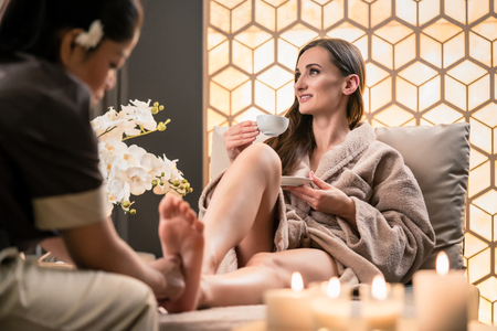 Photo pour Professional wellness therapist massaging the foot of a female client in Asian beauty center - image libre de droit