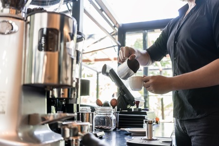 Foto de Side view of a young serious bartender pouring fresh milk into a cup of coffee behind the bar counter in a trendy cafeteria - Imagen libre de derechos