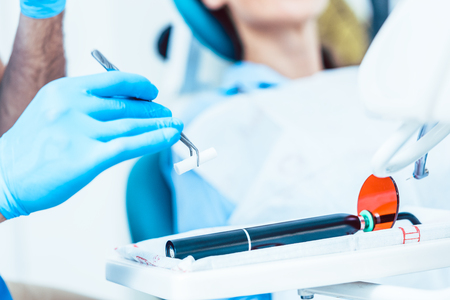 Photo pour Close-up of the hand of a dentist wearing sterile surgery gloves, while preparing a dental LED curing light machine for treating a patient in a modern clinic - image libre de droit