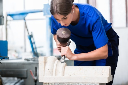 Photo for woman Stonemason carving pillar out of stone in her workshop - Royalty Free Image