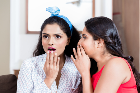 Photo pour Young woman whispering to her best friend gossips or funny secrets indoors - image libre de droit