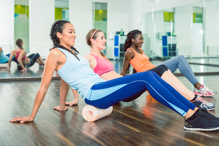 Photo for Side view of a fit beautiful woman smiling, while exercising on versatile foam roller during group workout class at a trendy fitness club with modern equipment - Royalty Free Image