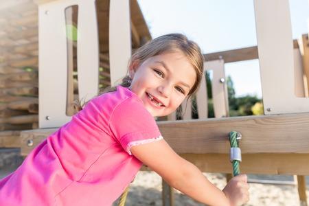 Foto de Little girl climbing on adventure playground already lost some teeth - Imagen libre de derechos