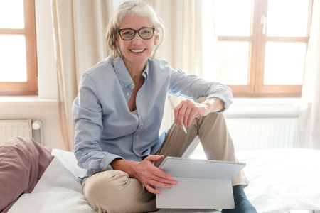 Photo for Senior woman freelancer in her study with computer sitting on the bed - Royalty Free Image