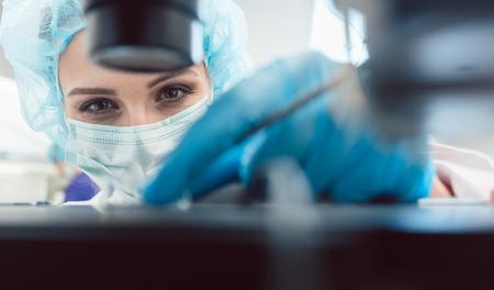 Photo pour Doctor or lab technician adjusting needle to fertilize a human egg under the microscope - image libre de droit