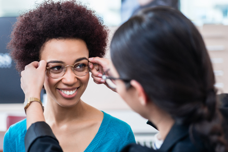 Photo for Optician showing woman new glasses and handing them to her - Royalty Free Image