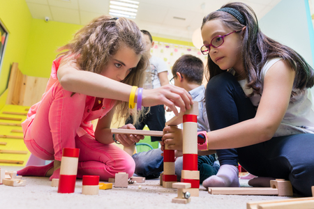 Foto de Two pre-school girls playing together with wooden toy blocks on the floor during playtime supervised by a careful young kindergarten teacher - Imagen libre de derechos