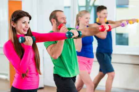 Photo pour Men and woman doing workout with small weights in fitness studio gym - image libre de droit