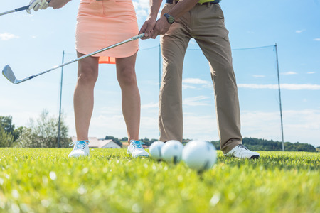 Photo pour Low section of man and woman holding iron clubs, while practicing together the correct grip and move for playing golf on the green grass of a professional ground - image libre de droit