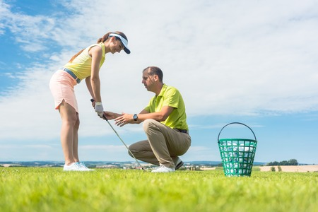 Photo pour Full length side view of a young woman holding an iron club, while exercising the golf swing helped by her experienced instructor outdoors on green grass - image libre de droit