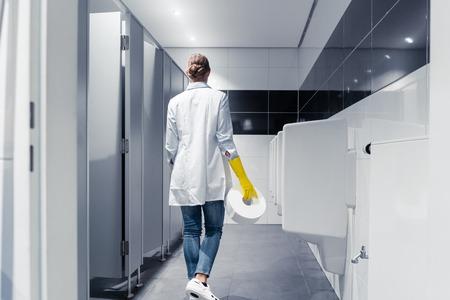 Foto de Janitor woman changing paper in public toilet or restroom - Imagen libre de derechos