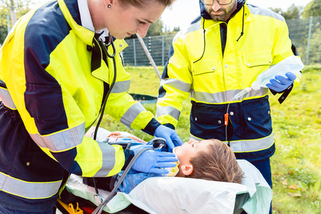 Foto de Paramedics measuring blood pressure of injured boy in front of ambulance - Imagen libre de derechos