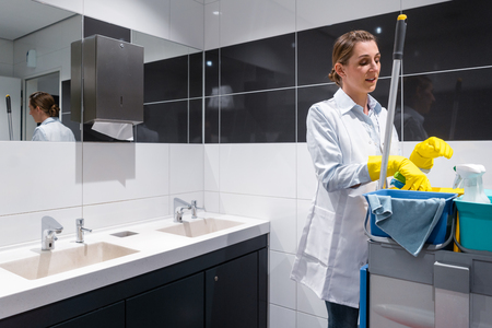 Photo for Janitor woman or charlady with her work tools looking at camera in toilet - Royalty Free Image