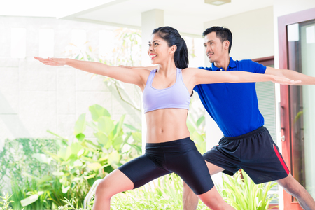 Photo for Happy Asian fitness couple at sport workout in tropical home - Royalty Free Image