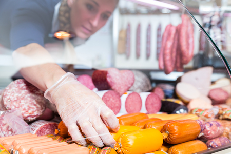Photo for Woman putting sausages and meat in butcher shop display, close-up - Royalty Free Image