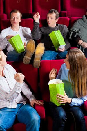 Foto de Group of people eating popcorn while man keeping legs on chair disturbing couple sitting in audience - Imagen libre de derechos