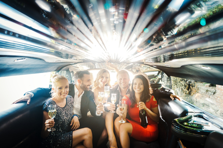 Photo for Celebration in a limo, woman and men drinking champagne and having a party - Royalty Free Image