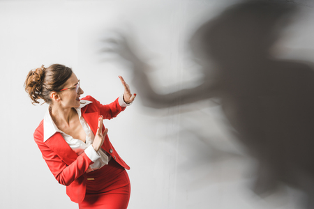 Photo for Businesswoman in red suit being harassed, symbolic picture with shadow - Royalty Free Image