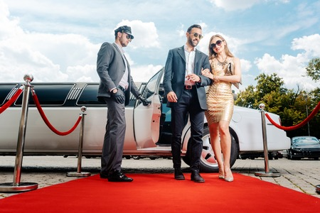 Foto per Couple arriving with limousine walking red carpet, a driver is opening the car door - Immagine Royalty Free