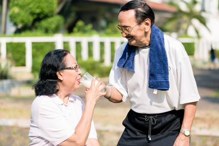 Photo for Close-up of smiling senior man giving milk glass to his wife - Royalty Free Image