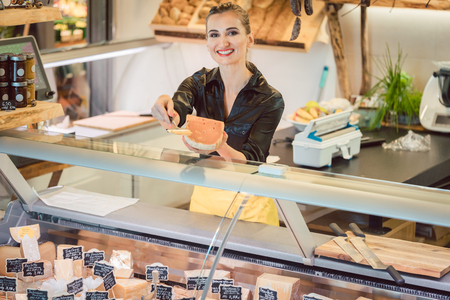 Photo for Beautiful woman offering cheese on delicatessen counter cutting a test bit off - Royalty Free Image