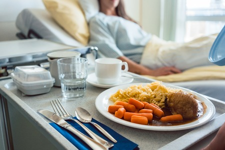 Photo pour Food delivered to a patient in hospital bed, focus on the meal - image libre de droit