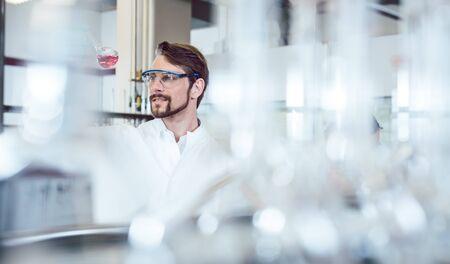 Foto de Research scientist man shot though bottles in his lab - Imagen libre de derechos