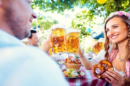 Foto de Couple looking at each other clinking glasses with huge amounts of beer in Bavarian pub - Imagen libre de derechos