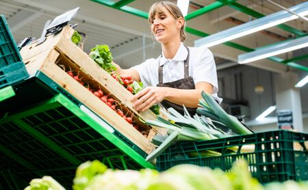 Photo for Woman working in a supermarket sorting fresh fruit and vegetables - Royalty Free Image