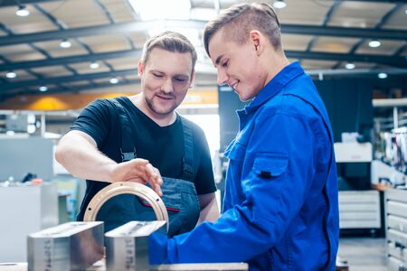 Photo for Skillful master discussing a workpiece with his apprentice or trainee - Royalty Free Image