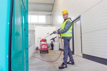 Foto de Worker cleaning a rental or mobile toilet with water hose - Imagen libre de derechos