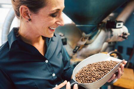 Foto de Woman in coffee roastery with fresh beans full of aroma - Imagen libre de derechos