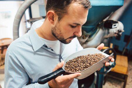 Foto de Man in coffee roastery with fresh beans in a little shovel - Imagen libre de derechos