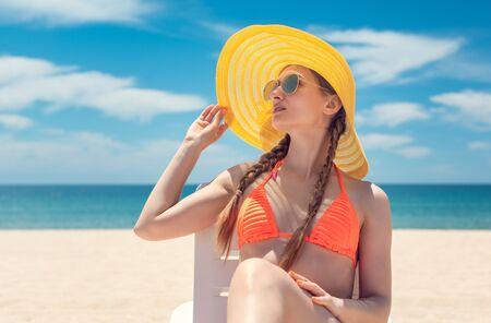 Foto de Woman with sun hat in deck chair on a beach by the sea tanning - Imagen libre de derechos